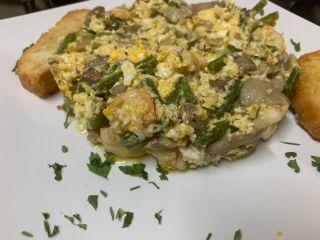 Scrambled eggs with mushrooms, prawns and young garlic